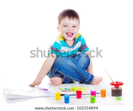 a studio portrait of a nice boy drawing with watercolor paint and brush isolated on white background - stock photo