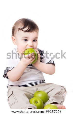 a studio portrait of a nice little child eating a green apple