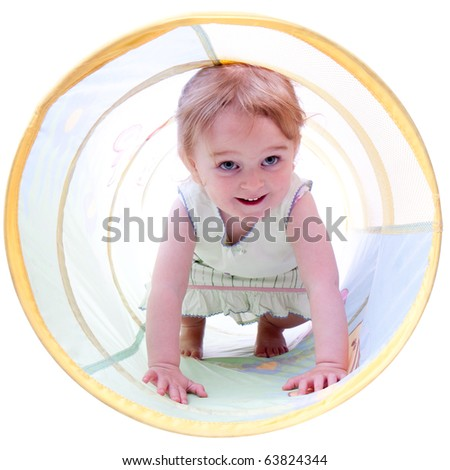 A studio portrait of a two year old girl crawling through a toy tunnel.
