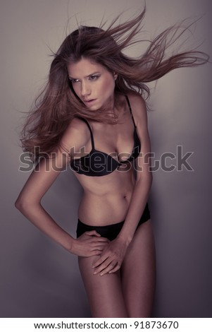 A studio shot of a beautiful, sexy girl with long, slightly fluttering in the wind hair, wearing black lingerie - stock photo