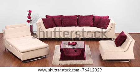 A studio shot of a modern furniture decorated with red pillows