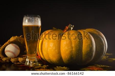 A studio shot of a pumpkin and a baseball glove, ball and a tall beer.