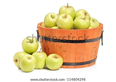 A studio shot of green apples in a wooden basket isolated on white background