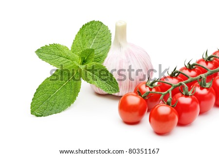 A studio shot of mint leaves, garlic and cherry tomatoes isolated on white background