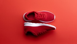 A studio shot of pair of running shoes on red background. Flat lay.