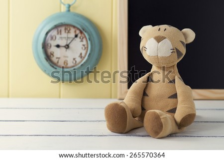 A stuffed animal on a white wooden table. In the background a turquoise clock and a blackboard on a yellow wainscot. Vintage