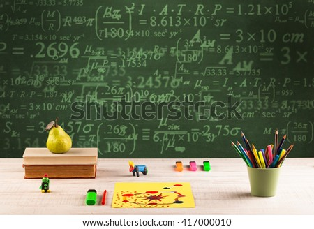 A stuffed school desk with green blackboard in the background full of numbers, calculation #417000010