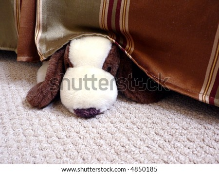 a stuffed toy dog hiding under a bed