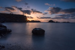 A stunning and colorful seascape  from a beautiful pebble beach at sunrise with some rocks in the background, Cabo de Palos, Murcia, Spain
