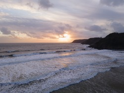A Stunning Coastal Sunset Full Of Colour Overlooking the Sea At Caswell Bay in Gower, Wales UK