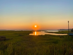 A stunning sunset over the marshy bay in Ocean City, Maryland.