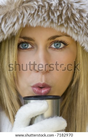 A stunningly beautiful young blond woman wrapped up warm and blowing onto a warm drink