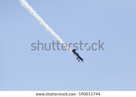A stunt plane trailing smoke at an airshow in Stuart FL