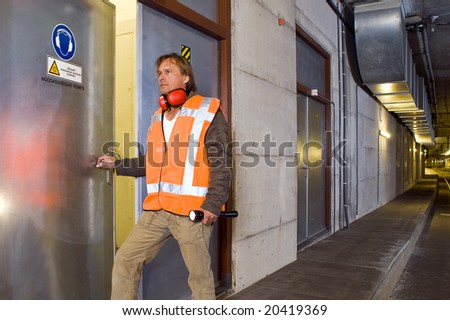 A sturdy looking engineer, opening a door to an engine room in a dimly lit tram tunnel, ignoring the safety precaution to wear his ear protection