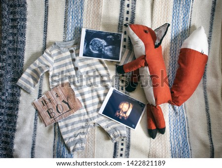 A styled pregnancy announcement of a baby boy with a striped onesie, ultrasound pictures, and a handmade fox stuffed animal all laid out on a blue and white blanket. It is an arial shot.