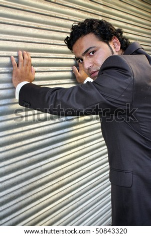 A stylish angry businessman posing near a shutter.