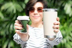 A stylish beautiful woman holding takeaway coffee cup in both hands, one is a single use paper cup with plastic lid the other one is a reusable stainless tumbler. Say no to plastic, No straw, 0 waste