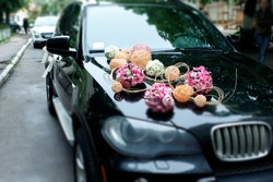 A stylish decoration of white flowers, ribbons and pink balls on a shiny bmw wedding car