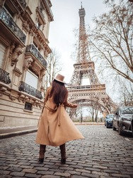A stylish girl in a beige coat, hat and boots stands on a small Parisian street with a view of the Eiffel Tower. Paris style.