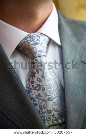 A stylish man in an expensive suit and tie and jacket, close-up. Unrecognizable.