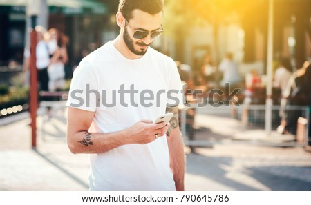 A stylish man with a tattoo and a beard wearing glasses and a white T-shirt in crowd uses his smartphone. Street photo