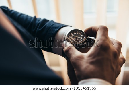 a stylish mechanical watch on the arm of a man dressed in a blue jacket with a white shirt that watches the time on the clock holding the clock by hand
