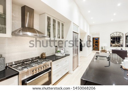 A stylish modular kitchen with a refrigerator next to it and a kitchen counter opposite the shelves and the stove.