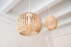 A stylish wicker wooden chandelier in boho and Bali style hangs on the ceiling near a white canopy made of weightless tulle. Part of the light airy interior.