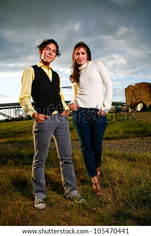 A stylish young couple stands in front of a dramatic sky in an empty lot in an urban setting.