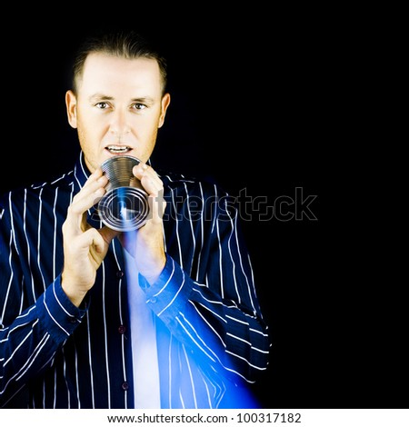 A stylish young man stands speaking into a tin can which is emitting a beam of audio communication in a Returning To Basics concept