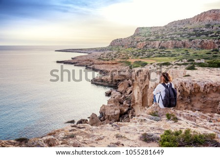 A stylish young woman traveler watches a beautiful sunset on the rocks on the beach, Cyprus, Cape Greco, a popular destination for summer travel in Europe