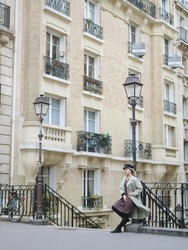A stylishly dressed blonde with blue eyes in a black cap and beige trench coat stands on a Parisian street near a street lamp. A French girl stands against the backdrop of Parisian architecture.