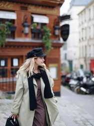 A stylishly dressed blonde with blue eyes in a black cap, black scarf and beige trench coat walks along a Parisian street near a cafe. French girl walking down the street.