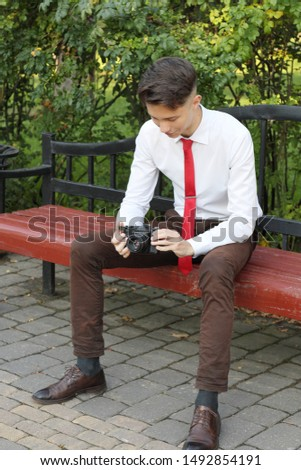 A stylishly dressed young man sits on a park bench. Stylishly dressed young man sits on a park bench. In his hands holds a SLR film camera.