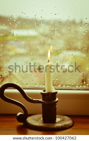 A stylized picture of a lit candle on a rainy day