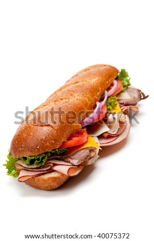A submarine sandwich with ham, turkey, roast beef, bacon, lettuce, tomato, cheese and onion on a white background