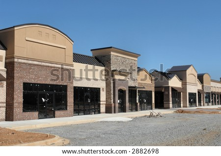 A suburban shopping center under construction.  A row of storefronts.