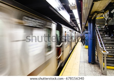 A subway is swifting by the platform of a subway station.