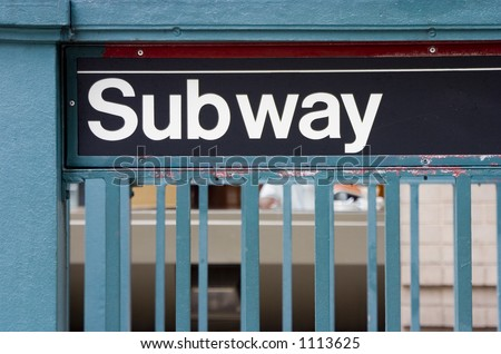 A subway sign at a sidewalk entrance, in New York City.