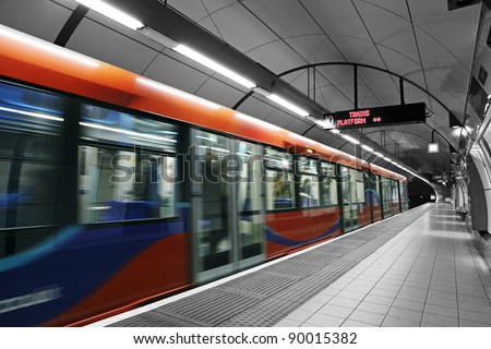 A subway train in motion arriving at a London underground train station.