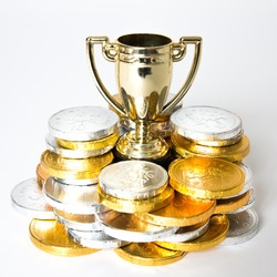 A success or victory concept with a gold trophy or cup surrounded by gold and silver coins in the form of prize money