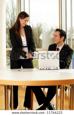 a successful business man with his secretary is bringing him a cup of coffee