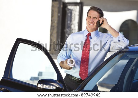 A successful businessman or architect holding plans & talking on his cell phone by a car