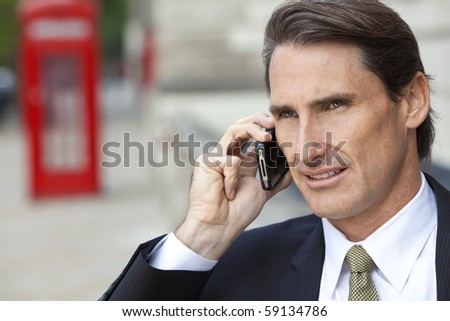 A successful businessman talking on his cell phone in London, England, with a classic red telephone box out of focus behind him