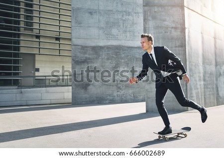A successful businessman wearing suit riding a skateboard in the street.