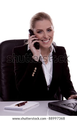 A successful businesswoman sitting at her desk  and talking on the phone. - stock photo