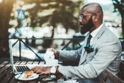 A successful handsome elegant bearded bald African businessman in a plaid costume and glasses is pouring tea into a cup while having a coffee break in an outdoor cafe, with a laptop in front of him