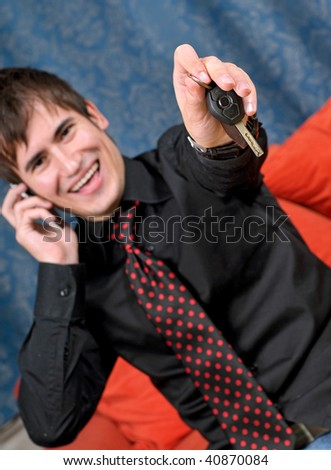 A successful man at home relaxing on the cell phone, offering his car keys to the viewer.