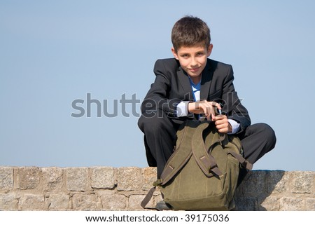 a successful school student is sitting on the stones and holding his schoolbag in his hands
