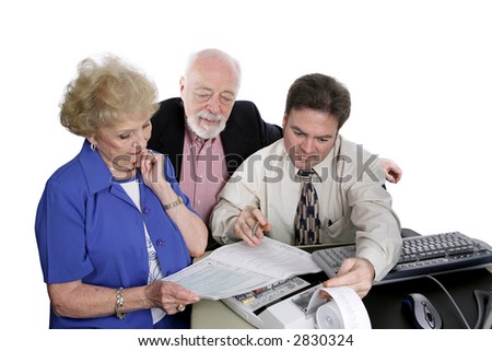 A successful senior couple going over figures with their accountant.